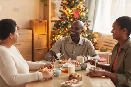Warm toned portrait of African-American family enjoying tea and snacks while celebrating Christmas at home Stockfoto