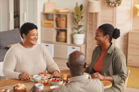 Warm toned portrait of African-American family enjoying tea and snacks while eating breakfast at home in cozy interior Stockfoto