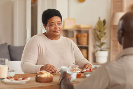 Portrait of senior African-American woman sitting at dining table during breakfast with family at home