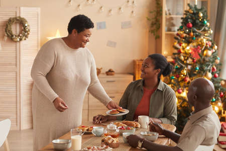Portrait of senior African-American woman serving homemade food for family at breakfast and smiling happily