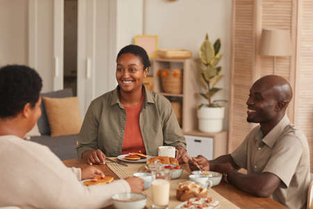 Portrait of smiling African-American woman sitting at dining table while enjoying breakfast with family at home Stockfoto