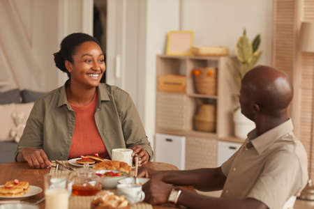 Portrait of smiling African-American couple sitting at dining table while enjoying breakfast with family at home