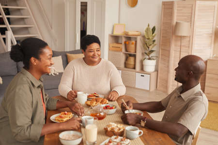 Warm toned portrait of happy African-American family sitting at dining table while enjoying breakfast at home Stockfoto