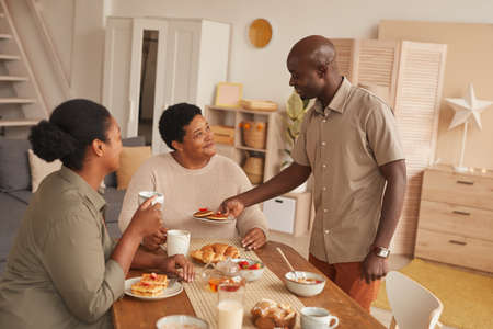 Warm toned portrait of happy African-American family enjoying breakfast at home in cozy interior