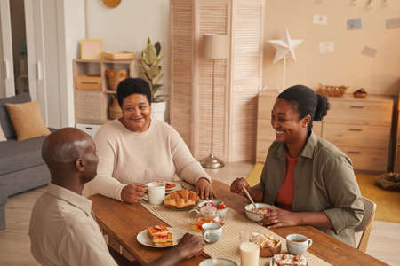 High angle portrait of happy African-American family sitting at dining table while enjoying breakfast at home