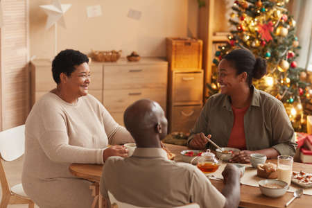 Portrait of happy African-American family sitting at dining table while enjoying breakfast on Christmas morning at home