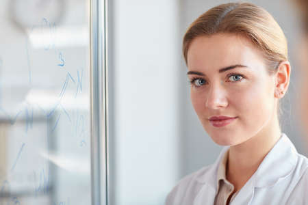 Close up portrait of blonde female scientist looking at camera while standing by glass wall with writings in medical laboratory, copy space
