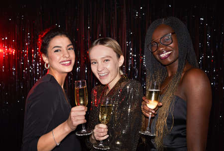 Waist up portrait of three elegant young women holding champagne glasses and smiling at camera while posing against sparkling background at party, shot with flash Stok Fotoğraf
