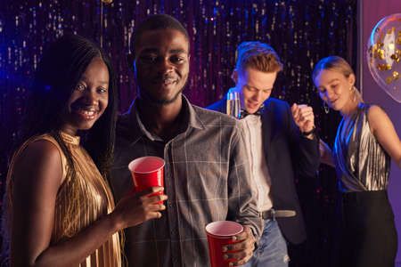 Portrait of young African-American couple smiling at camera while enjoying prom night, copy space