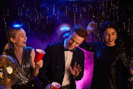 Portrait of three happy teenagers dancing and laughing while enjoying prom night