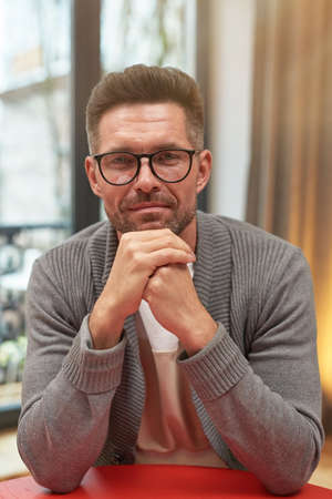 Vertical portrait of handsome mature man wearing glasses and smiling at camera while working at home office Stok Fotoğraf