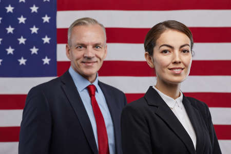 Portrait of two smiling politicians looking at camera while standing against USA flag background, copy space