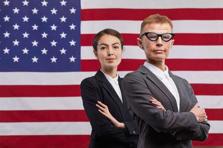 Waist up portrait of two confident female politicians looking at camera while standing with arms crossed against USA flag background, copy space