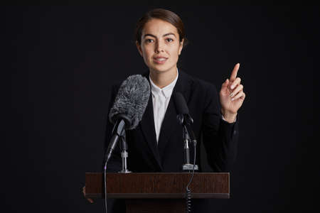 Waist up portrait of young female speaker standing at podium and giving speech to microphone against black background, copy space Standard-Bild