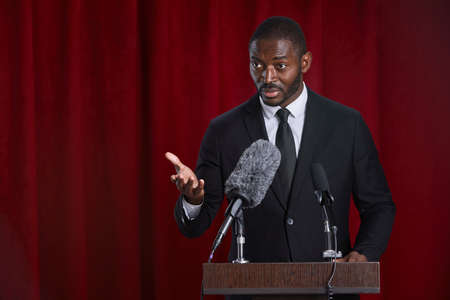 Waist up portrait of African-American man speaking to microphone standing at podium on stage against red curtain, copy space Фото со стока