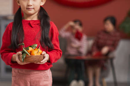 Medium section shot of modern Chinese girl holding wooden bowl full of fresh tangerines, Lunar New Year traditions concept Banque d'images