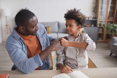 Portrait of African-American father fist bumping smiling son while doing homework together at home