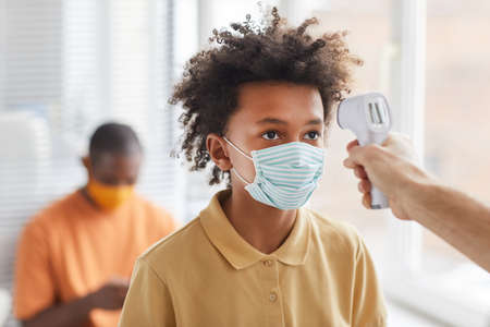 Portrait of teenage African-American boy wearing mask getting temperature check while waiting in line at clinic, copy space