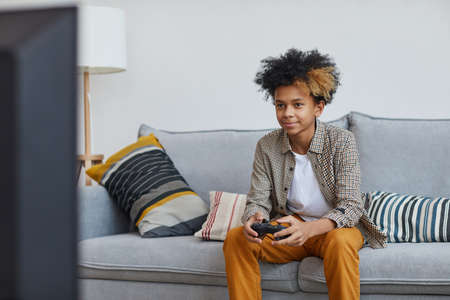 Minimal portrait of teenage African-American boy playing video games at home and smiling happily while holding gamepad, copy space Stock Photo