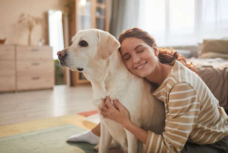 Warm toned portrait of smiling young woman embracing dog while sitting on floor and enjoying time with loving pet, copy space