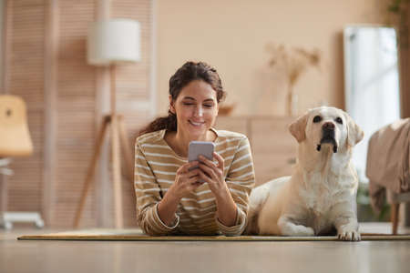Front view portrait of smiling young woman lying on floor with dog and using smartphone in cozy home interior, copy space Imagens