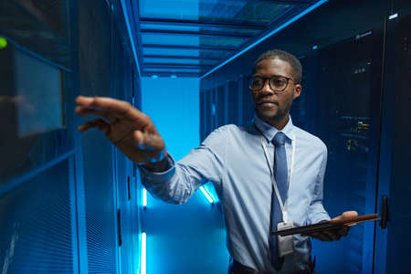 Waist up portrait of African American man reaching for server cabinet while working with supercomputer in data center and holding tablet, copy space Stock fotó