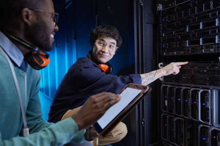 Portrait of two young technicians setting up server network while working in data center, copy space Stock fotó
