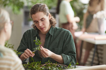Portrait of young male florist cutting green plants while creating floral compositions for decor, copy space Stock Photo