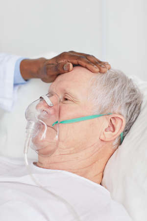 Close up of African-American doctor comforting senior patient lying in hospital bed with oxygen mask