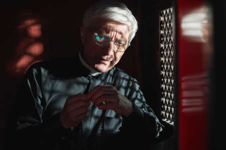 Senior priest sitting with rosary beads sitting in confessional and listening to confession Stock Photo