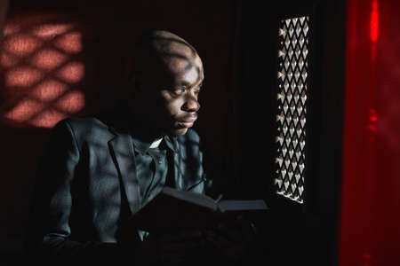 African priest reading the Bible while sitting in the confessional