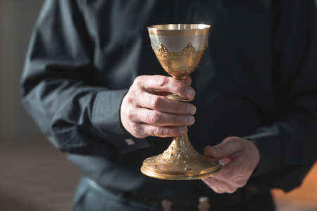 Close-up of senior priest holding the cup in the church