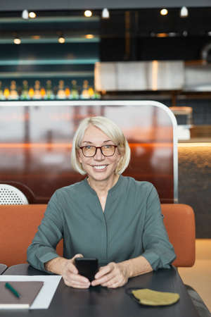 Portrait of cheerful blond-haired Caucasian businesswoman in eyeglasses holding smartphone and smiling at camera in modern cafe Standard-Bild