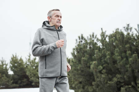 Serious senior Caucasian man in gray sport suit swinging arms while running alone in forest