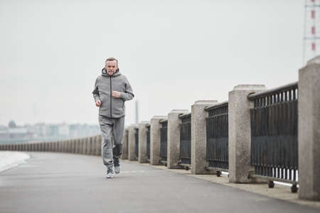 Purposeful senior Caucasian man in gray sport suit swinging arms while running alone in cold morning