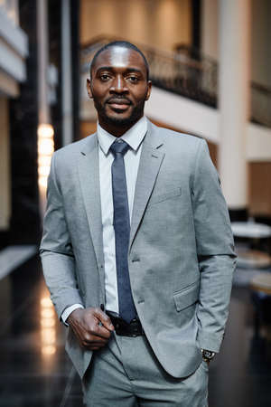 Vertical portrait o successful African-American businessman looking at camera while standing at luxurious hotel lobby