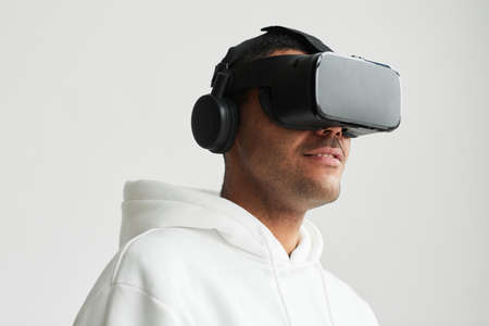 Minimal portrait of modern man wearing VR headset against white background, copy space