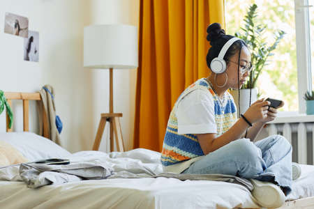 Side view portrait of trendy teenage girl playing mobile game vi smartphone while sitting on bed in cozy room, copy space