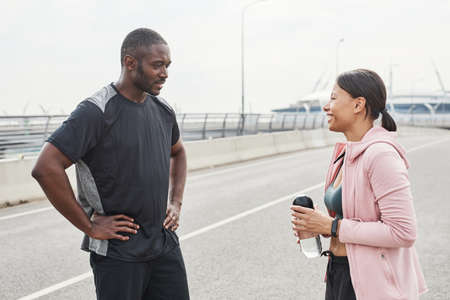 Young couple in sports clothing discussing training together while standing in the city