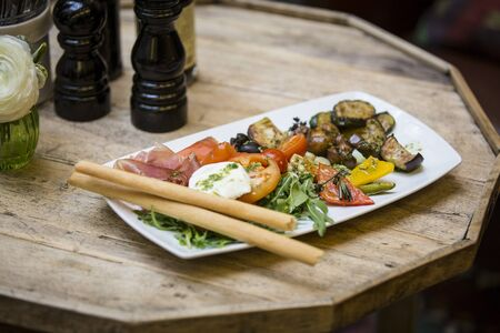 antipasti: Appetizer plate in restaurant with Italian antipasti and table decorations
