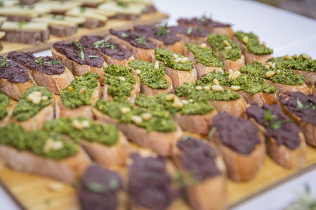 Catering  sandwiches with vegetable spread on wooden board