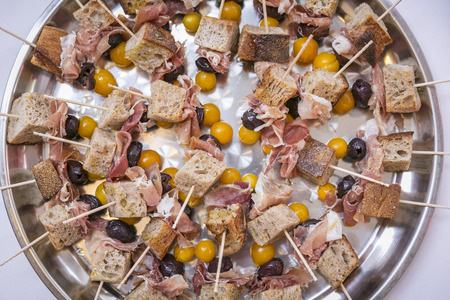 Catering  skewers with bread, ham, physalis & grapes