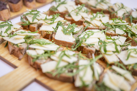 Catering  sandwiches with cheese and ruccola on wooden board