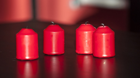 unlit: Some unlit blown out red candles on a black table.