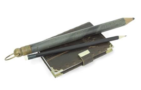 L�pices antiguos y modernos con el libro de notas est�n aislados en el blanco  Foto de archivo - 6927867