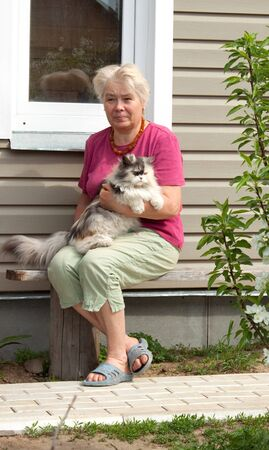 Woman sits on summer residence with thoroughbred cat on hands