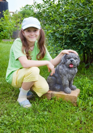 view girl: Smiling little girl near to concrete dog in garden