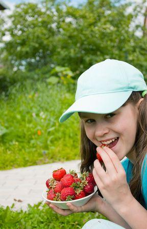 Little girl eats ripe strawberry in garden photo