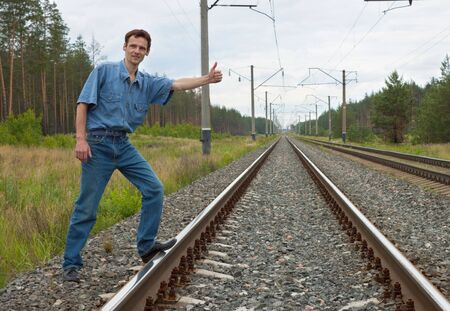 Man on railway with the lifted hand stops  train