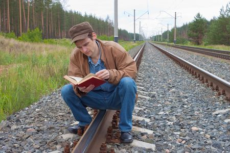 Man sits on railway and with enthusiasm reads book Stock Photo - 7212772
